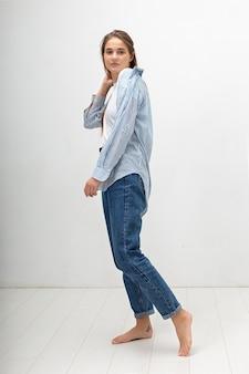Retrato de joven mujer caucásica con pelo largo en camiseta, jeans y camisa a rayas sobre fondo blanco de estudio. bonita mujer en ropa casual posando con los pies descalzos en el piso