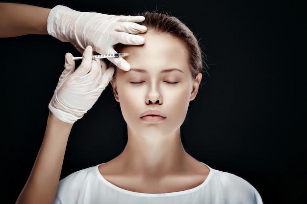 Retrato de joven mujer caucásica recibiendo inyección cosmética