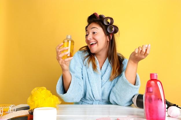 Retrato de joven mujer caucásica en su rutina de belleza día, piel y cuidado del cabello. modelo de mujer con cosmética natural aplicando cremas y aceites de maquillaje. cuidado corporal y facial, concepto de belleza natural.