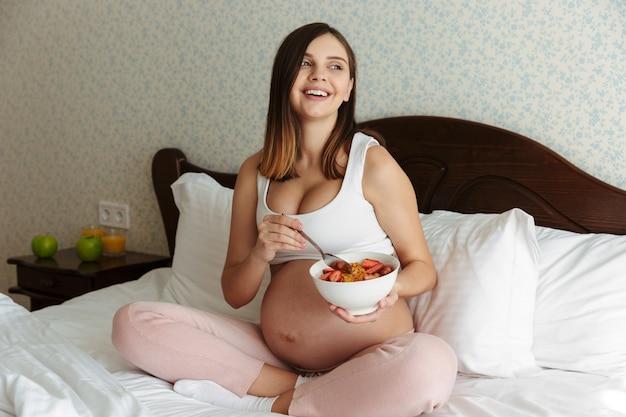 Retrato de una joven mujer embarazada riendo