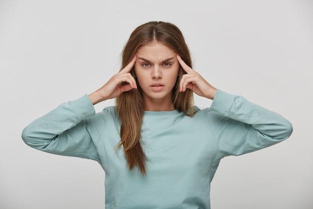 Retrato de joven mujer encantadora y atractiva que sufre de dolor de cabeza