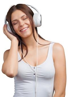 Retrato de una joven mujer escuchando música con auriculares