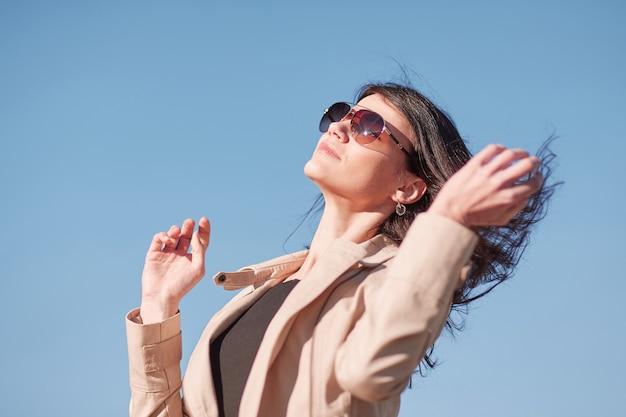 Retrato de una joven mujer exitosa contra el cielo