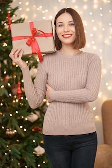 Retrato de joven mujer feliz con labios rojos mirando a la cámara sosteniendo una caja de regalo envuelta
