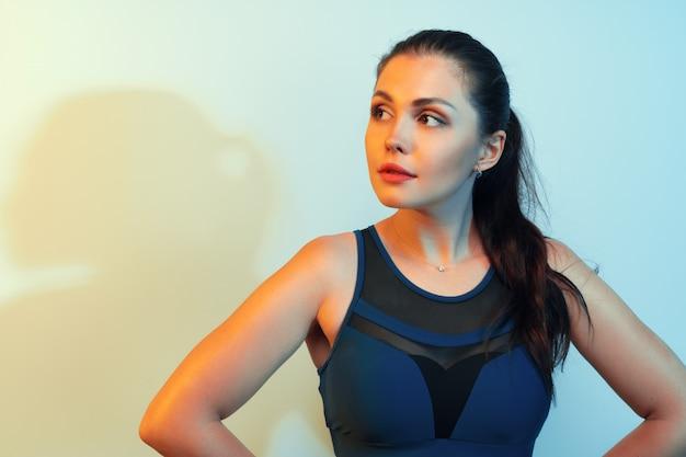 Retrato de una joven mujer fitness en ropa deportiva posando en studio
