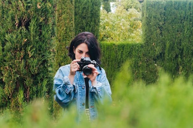 Retrato de joven mujer fotógrafa tomando foto de la naturaleza con cámara