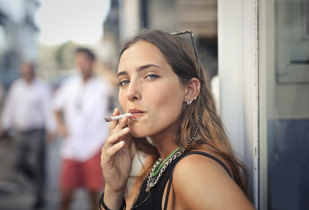 Retrato de una joven mujer fumando en la calle