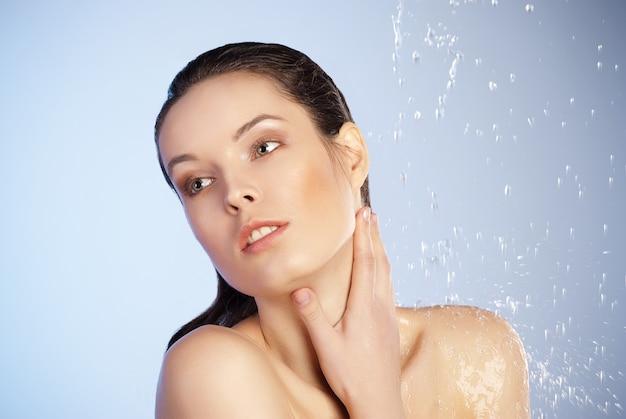 Retrato de joven mujer hermosa sensualidad bajo el chorro de agua - fondo azul