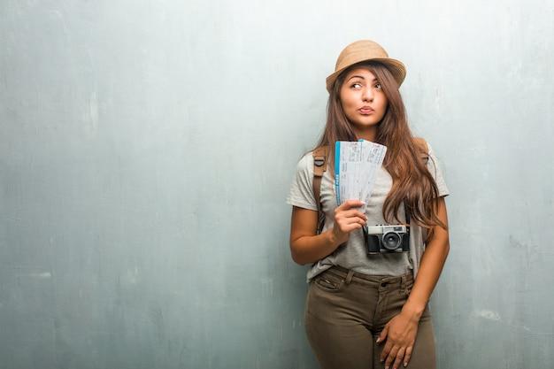 Retrato de una joven mujer latina que viaja contra una pared dudosa y confundida, pensando en una idea o preocupada por algo.
