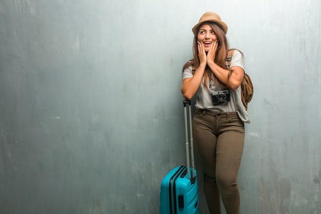 Retrato de una joven mujer latina que viaja contra una pared sorprendida y conmocionada, mirando con los ojos muy abiertos.