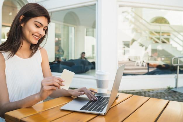 Retrato de joven mujer latina con tarjeta de crédito y usando laptop para comprar en línea en una cafetería. compras en línea y concepto de estilo de vida.