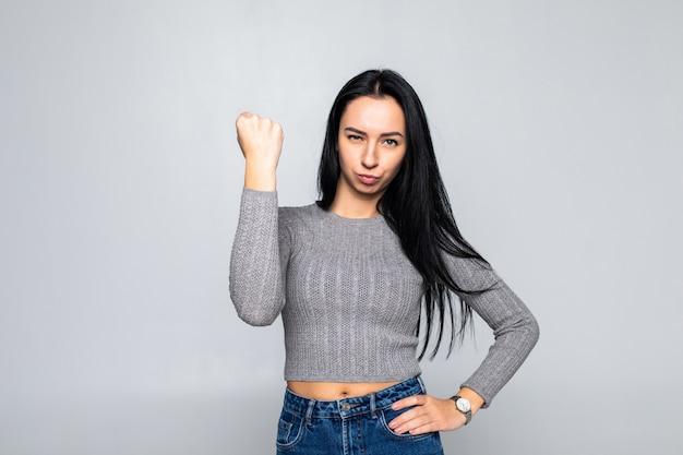 Retrato de joven mujer morena dominante mostrando el puño en la pared gris