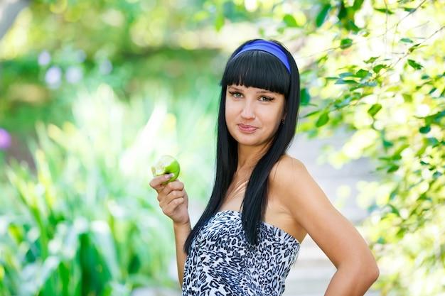 Retrato joven mujer morena encantadora mordiendo manzana verde fondo parque de verano
