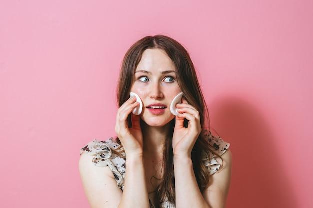 Retrato de joven mujer morena limpiando su rostro con almohadillas de algodón