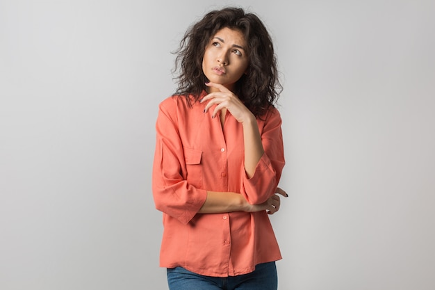 Retrato de joven mujer morena pensativa en camisa naranja, cabello rizado, estilo veraniego, expresión de la cara frustrada, mirando hacia arriba, pensando, problema, idea, raza mixta, aislado
