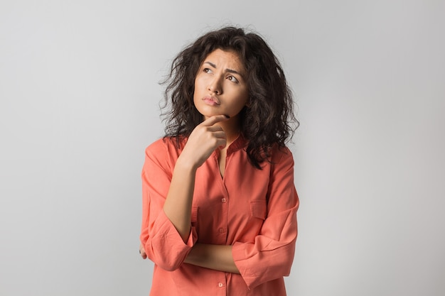 Retrato de joven mujer morena pensativa en camisa naranja
