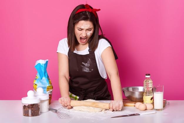 Retrato de joven mujer morena que trabaja en la cocina, preparar pasteles caseros, se ve cansado y enojado. atractivo panadero amasa y usa harina, se para cerca de la mesa con un rodillo, grita algo.