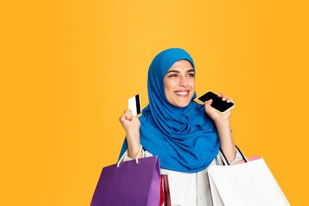 Retrato de joven mujer musulmana aislada sobre fondo amarillo studio