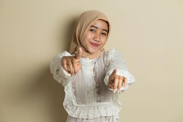 Retrato de joven mujer musulmana asiática con hijab sonriendo mientras apunta hacia adelante