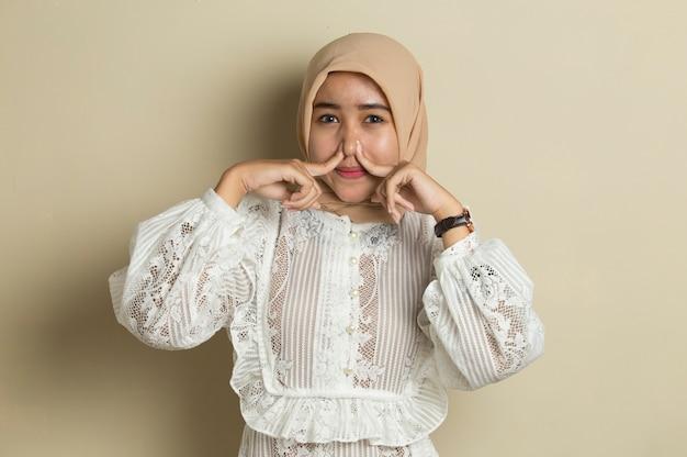Retrato de joven mujer musulmana asiática con hiyab tapándose la nariz debido a un mal olor