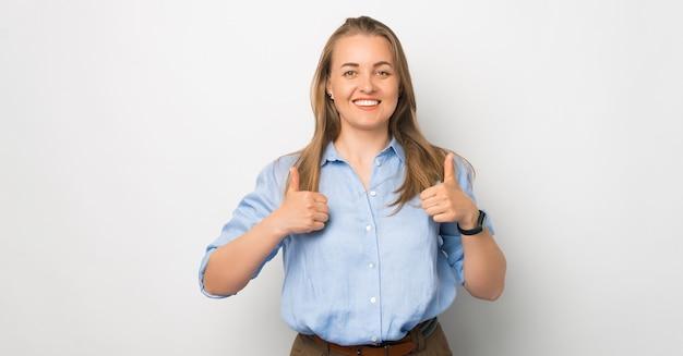 Retrato de joven mujer de negocios en casual mostrando thumbs up sobre fondo blanco.