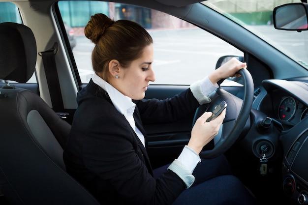 Retrato, de, joven, mujer de negocios, conducir un coche, y, utilizar, teléfono
