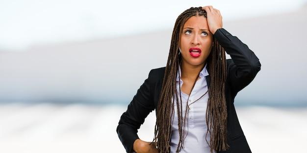 Retrato de una joven mujer de negocios negra preocupada y abrumada, olvidadiza, se da cuenta de algo, expresión de shock por haber cometido un error