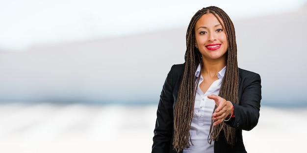 Retrato de una joven mujer de negocios negra que llega a saludar a alguien o gesticula para ayudar, feliz y emocionada