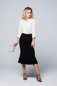 Retrato de una joven mujer de negocios profesional con un amplio espacio de copia aislado en la pared blanca.