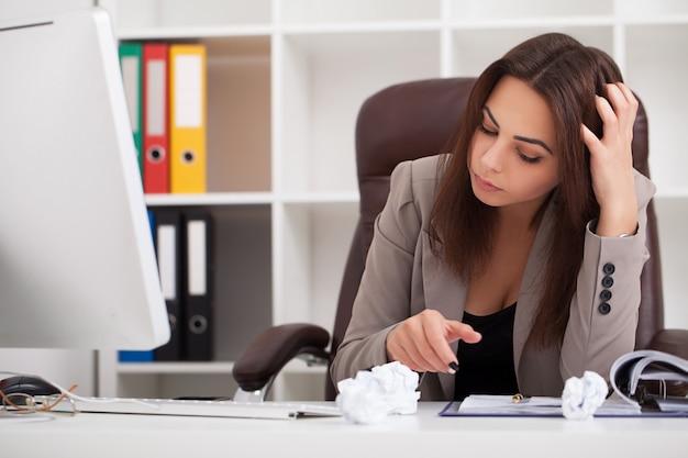 Retrato de joven mujer de negocios en su oficina