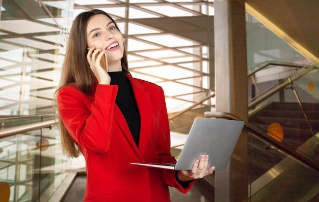 Retrato de una joven mujer de negocios usando laptop