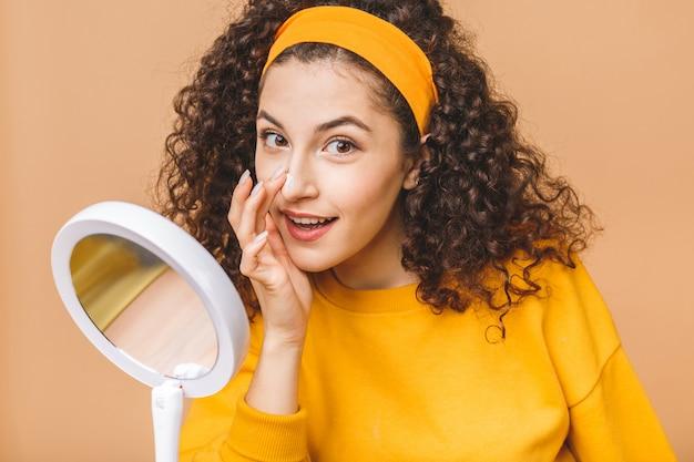 Retrato de joven mujer rizada con crema para la piel en un espejo aislado sobre fondo beige. concepto de cuidado de la piel.