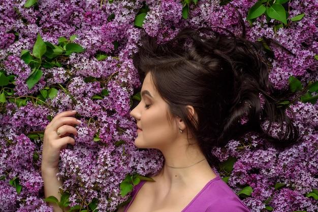 Retrato de una joven mujer rodeada de lilas. una mujer está parada de lado.
