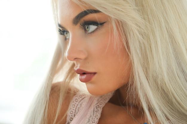 Retrato de joven mujer rubia con piel bronceada y ropa de moda