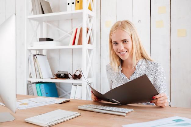 Retrato de una joven mujer rubia sosteniendo una carpeta abierta en su lugar de trabajo