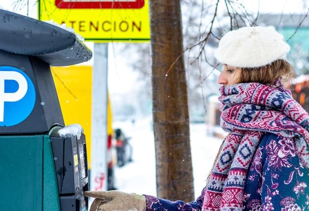 Retrato de una joven mujer rubia vestida con ropa de invierno obteniendo un boleto para la máquina de estacionamiento en una avenida nevada de la ciudad.