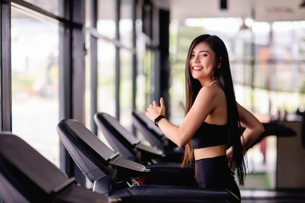Retrato de joven mujer sana corriendo en caminadora, sonríe durante el entrenamiento en el gimnasio, concepto de estilo de vida saludable, imagen vertical del espacio de copia