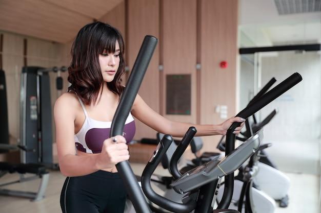 Retrato de joven mujer sana y deportiva con máquina de ejercicio en el gimnasio