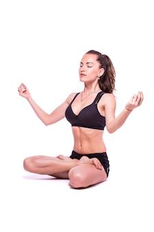 Retrato de una joven mujer sana haciendo ejercicios de yoga, aislado sobre fondo blanco.