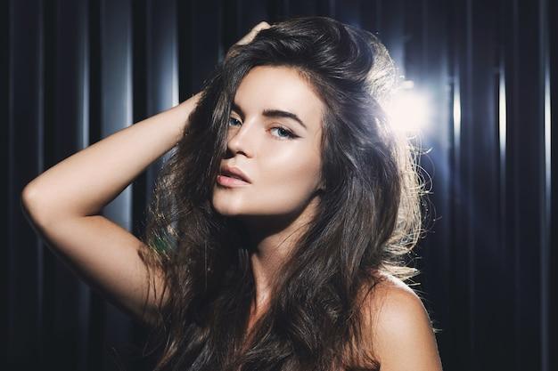 Retrato de joven mujer sexy posando en la oscuridad con luz de fondo