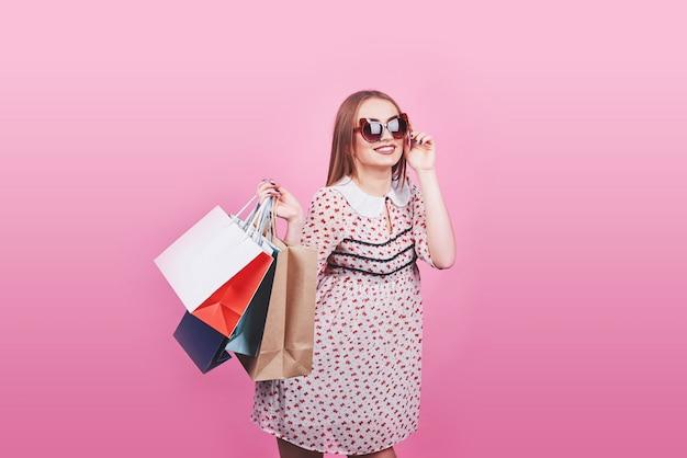 Retrato de joven mujer sonriente feliz con bolsas de compras en rosa