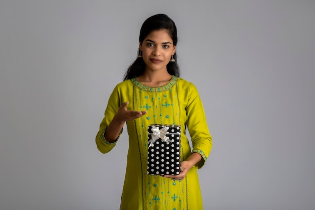 Retrato de joven mujer sonriente feliz chica con caja de regalo en un gris.
