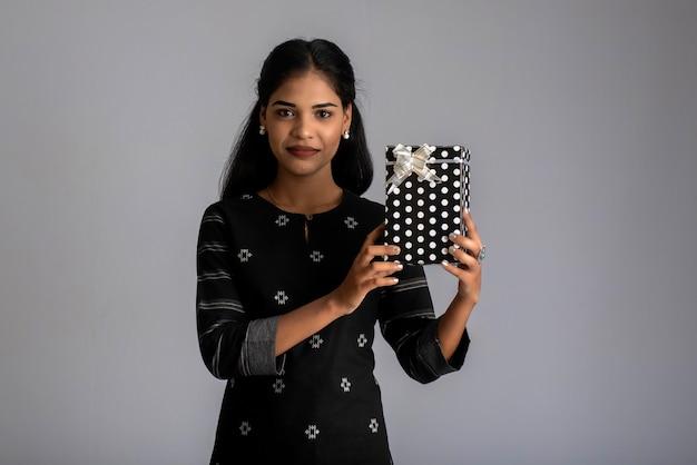 Retrato de joven mujer sonriente feliz chica con caja de regalo sobre un fondo gris.