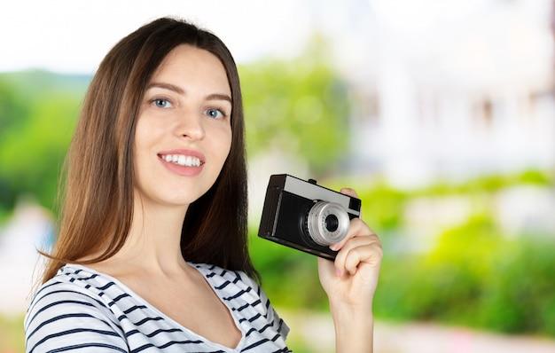 Retrato de una joven mujer sonriente filmando con cámara retro aislada