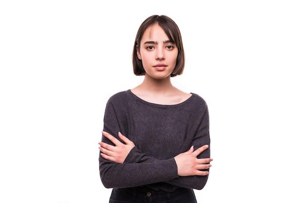 Retrato de joven mujer sonriente de pie con las manos juntas
