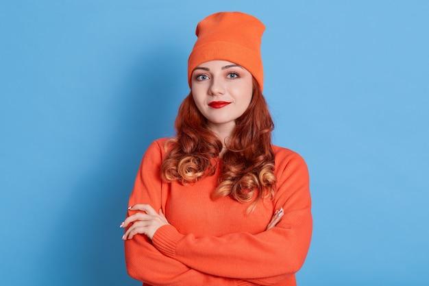 Retrato de joven mujer sonriente en suéter naranja y gorra, de pie con los brazos cruzados