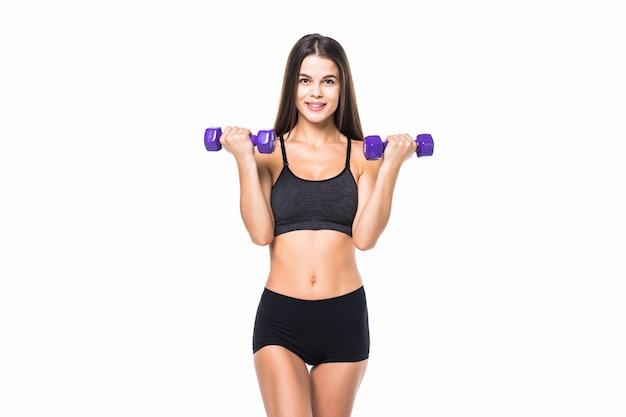 Retrato de una joven mujer sosteniendo pesas y haciendo fitness contra blanco