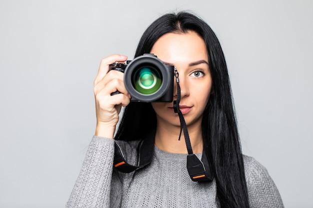 Retrato de una joven mujer tomando fotos en la cámara, aislada en la pared gris