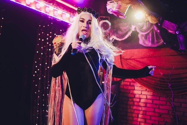 Retrato de joven mujer transgénero en traje brillante sobre fondo de color.