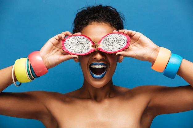Retrato de joven mulata con pulseras en sus brazos divirtiéndose cubriendo los ojos con fruta pitahaya madura cortada por la mitad, aislado en azul